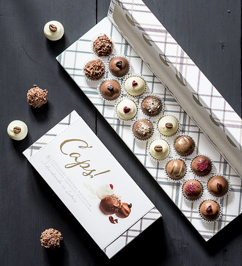 The light, smartly chequered CAPS! boxes house truffles dressed in white and milk chocolate. Rhubarb- peppermint, cranberry, gooseberry-clove, blackcurrant, rowan and strawberry. All of these and others reside here – in a box of sweet moments. To pamper you and others.