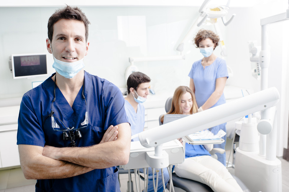 A portrait of a dentist with his team wo