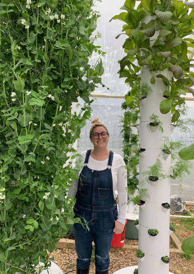 Farm Manager Emilie with hydroponic towers