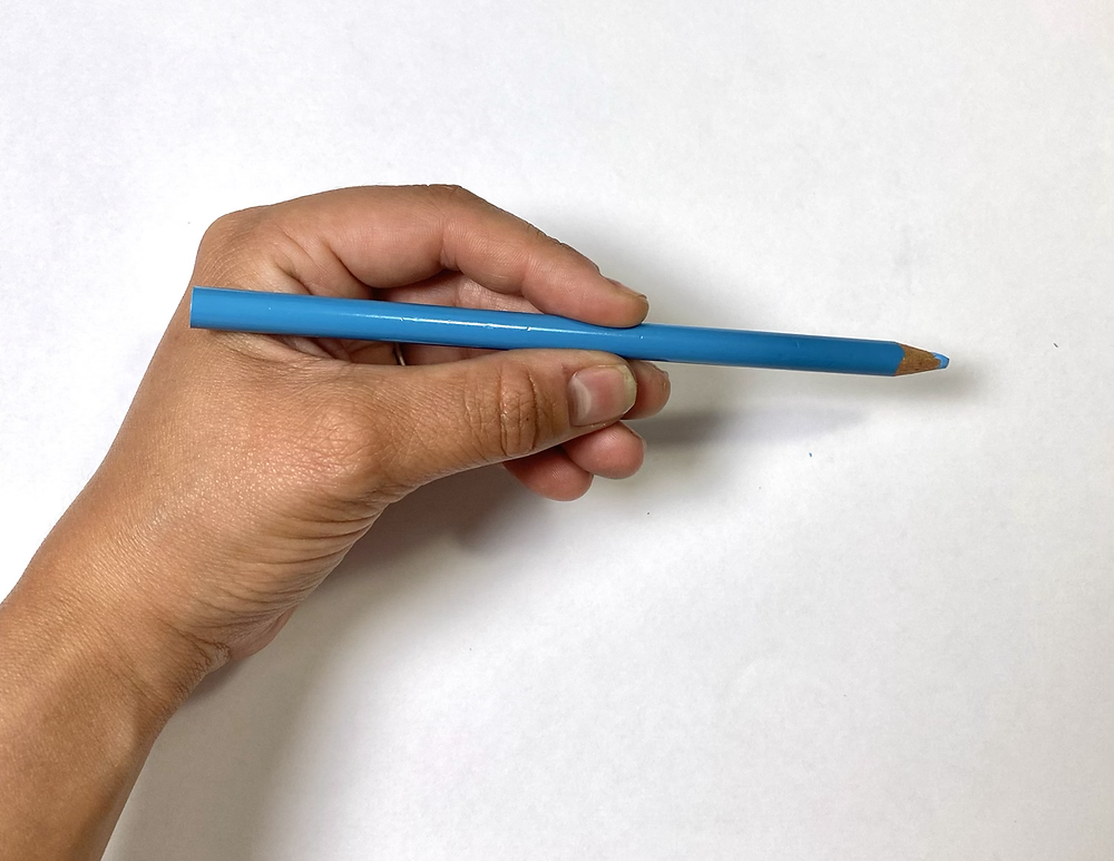 A close up of a hand holding a blue pencil crayon. The background is simple and light