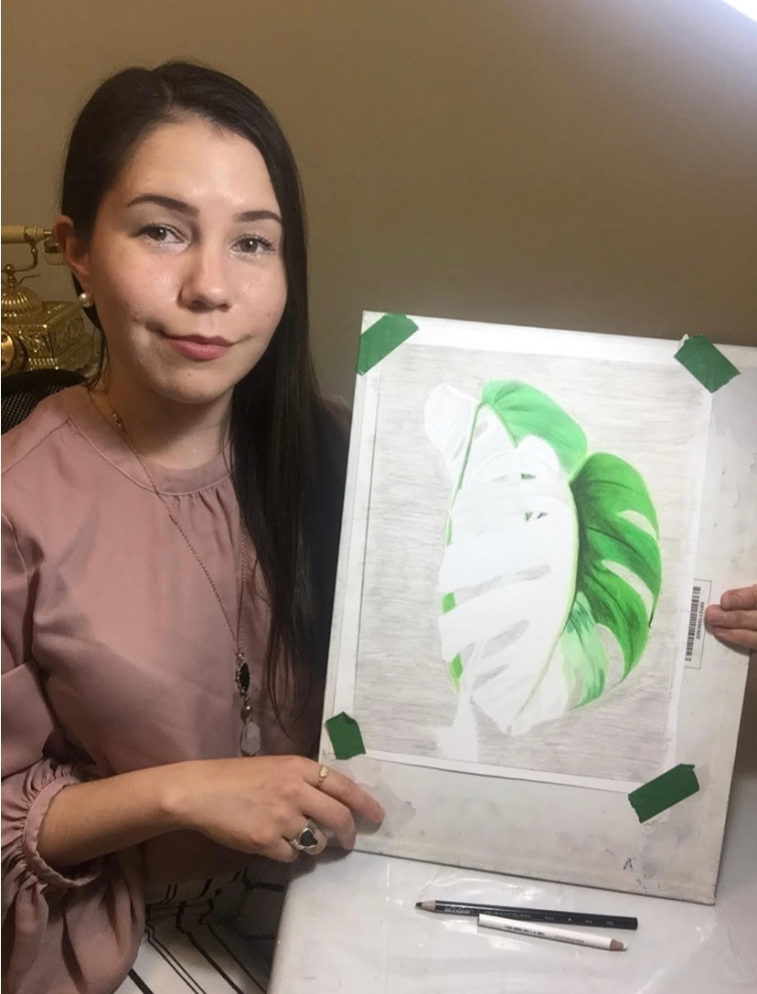 Saskatoon artist Kas Rea holding an artwork of a plant