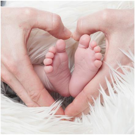 Babyfoto kleine Füße - liebende Hände