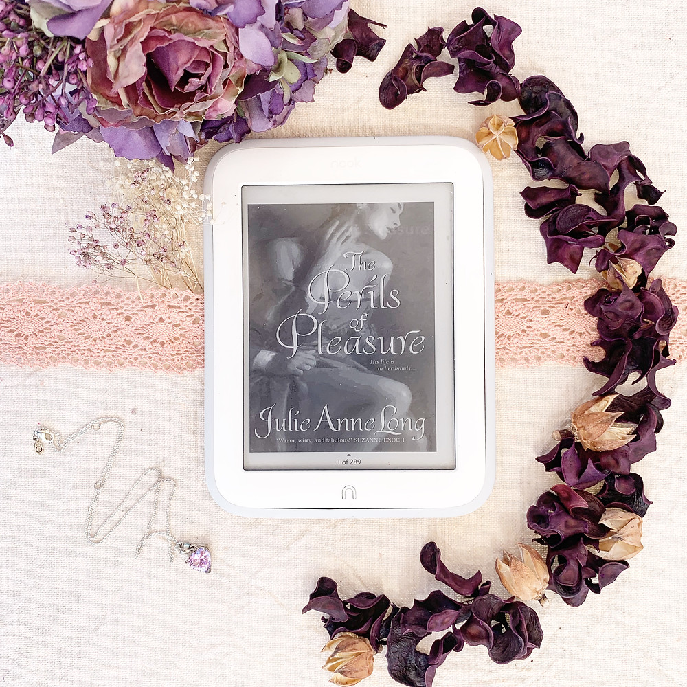 Nook book displaying the cover of the book on a table with flowers, ribbon, and a necklace