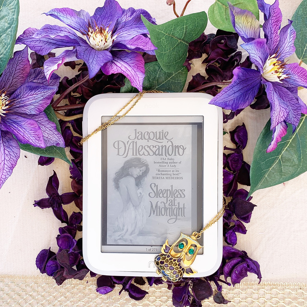 Clematis flowers above a nook book displaying the cover, wrapped with a necklace featuring an owl.