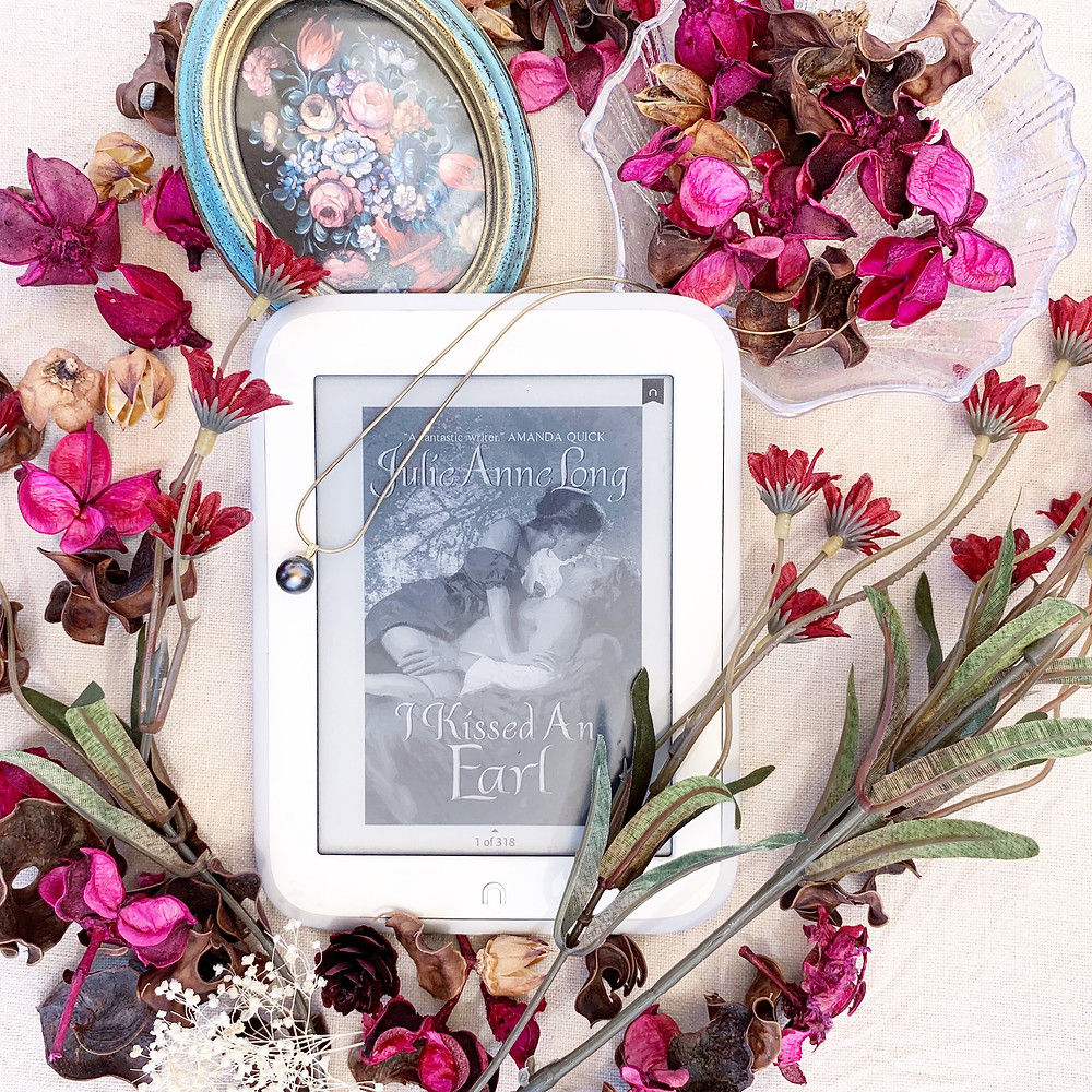 A nook book featuring the cover, flowers, a miniature painting, a pearl necklace, and a seashell glass dish.