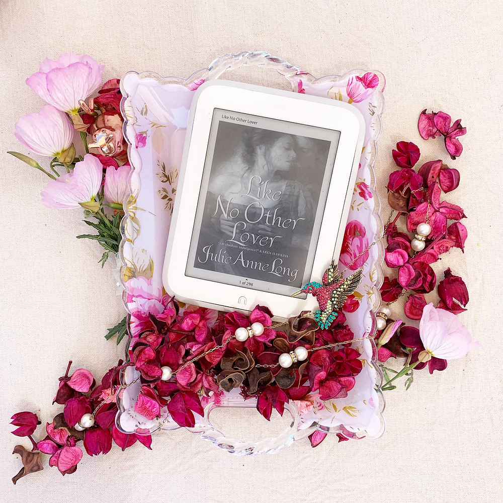 Nook book displaying the cover on a tray with some flower petals and a few pieces of jewelry.