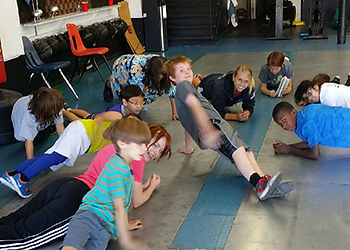 Samantha Achterberg World Champion doing push-up with kids at Cheyenne Fencing Society and Modern Pentathlon Center