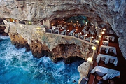 An empty sophisticated restaurant inside a cave overlooking the Adriatic Sea in Puglia. An unusual location, where our incentive, event planners and meetings, conferences planners use for a unique corporate event in Italy.