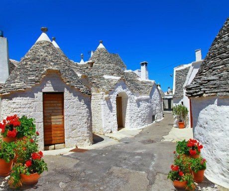 White stone huts, or Trullis, with beautiful ceramic pots with red flowers in a sunny day  in the Unesco site in Alberobello, Puglia,   Italy