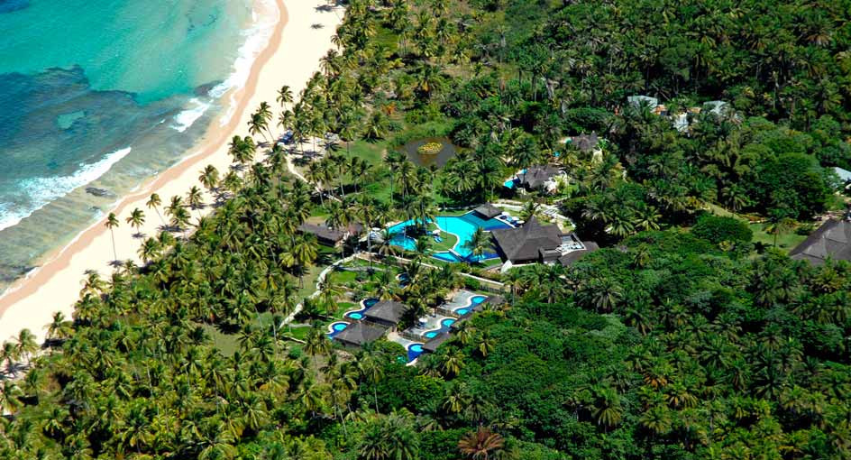 A beautiful aerial view of the Anaranta Resort in Maraú Bahia with its huts and swimming pool surrounded by high tropical palm trees at the beachfront. A perfect place for incentives.
