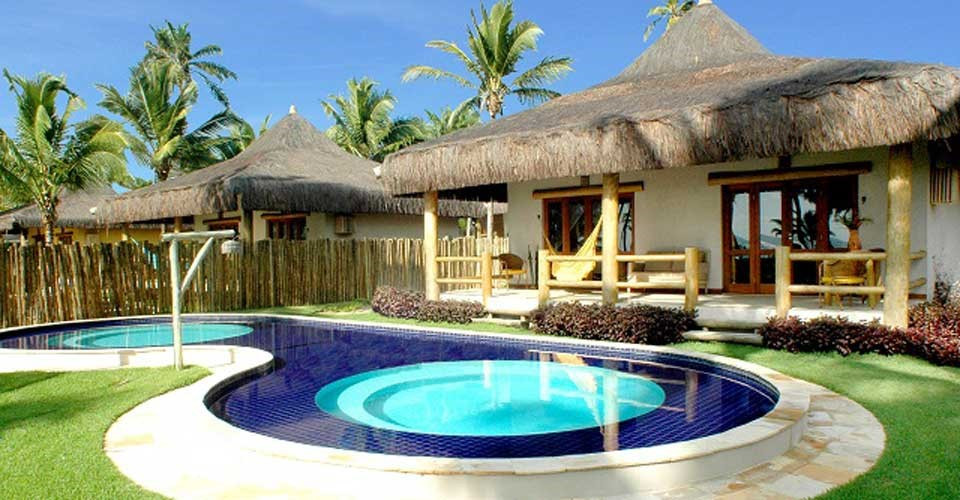 Two rustic huts with a swimming pool in front at the Marau Resort in Bahia, Brazil.