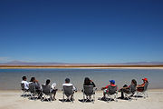 A group of 8 people siiting in charis faceing the beautiful and wild lake of Atacama Desert as if they were in an incentive or copany retreat event with our DMC Brazil