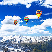 Three colourful hot air balloons flying over the snowy mountains of Patagonia, Chile,  in an incentive trip, representing our DMC Brazil Event Management and Planning services