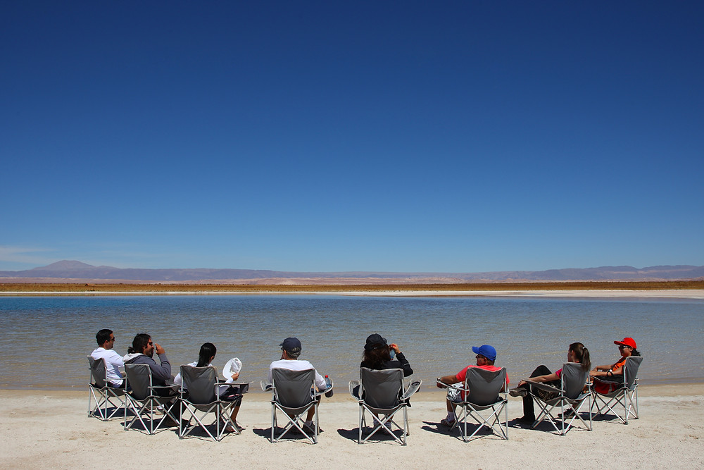 8 people sitting in from of a lake at the Atacama Desert in Chile