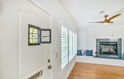 Front door shot to window seat fireplace