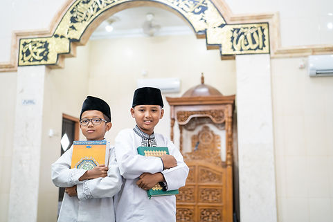 portrait of two boys holding holy quran