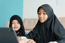 Two Muslim girl is studying online via t
