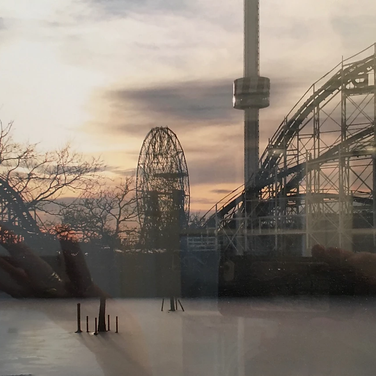 Meridith McNeal, My hands reflected in the frame on a photo of Coney Island in the snow.