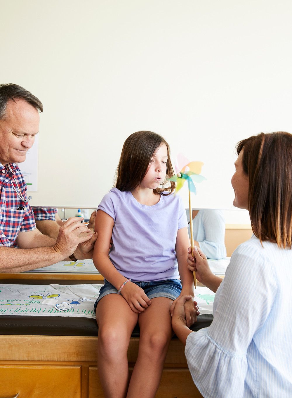 child blowing pinwheel while getting a shot at the doctor