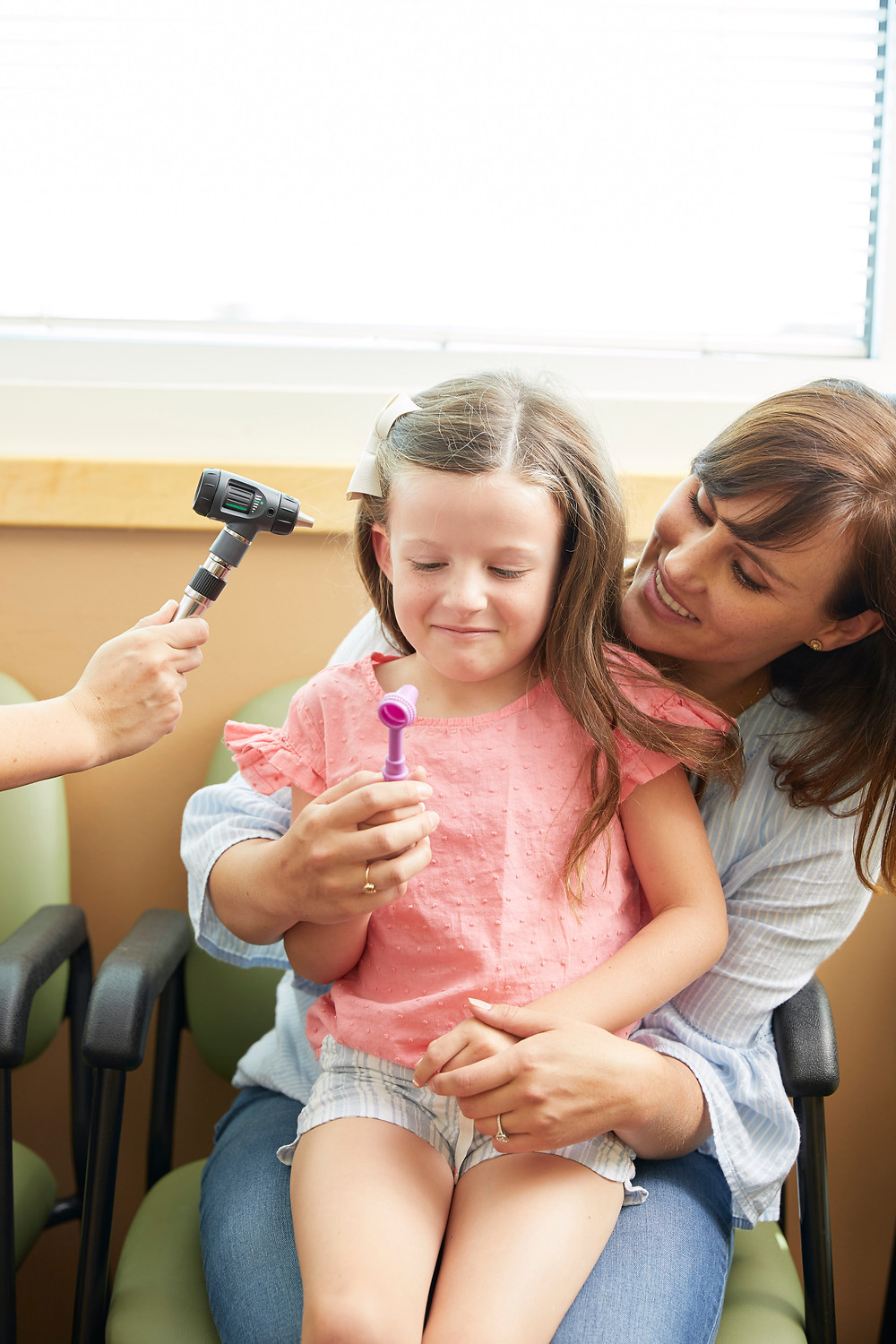 child looking at otoscope at doctor