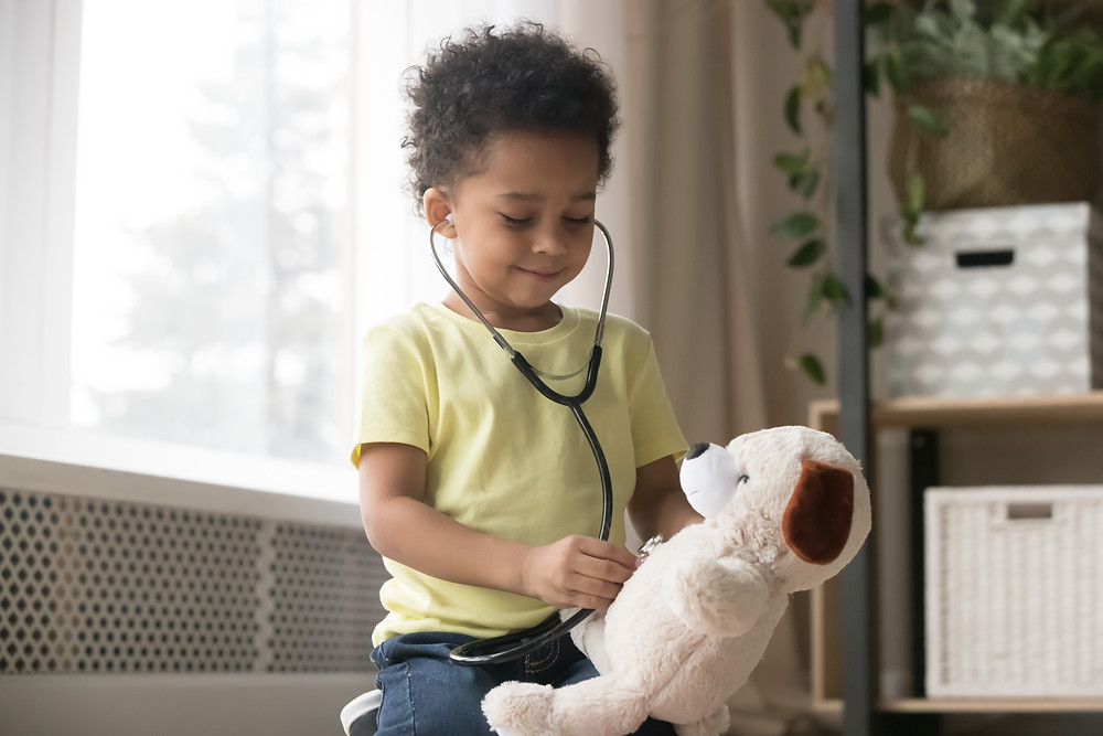 child smiling with stethoscope and stuffed animal