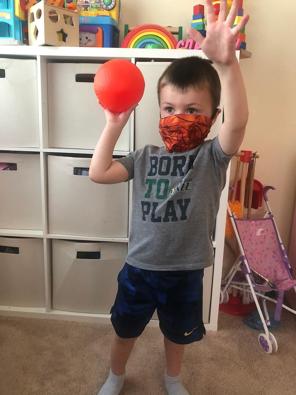 child wearing basketball mask playing basketball