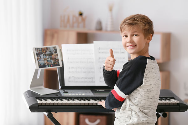 Little boy taking music lessons online a