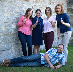 Motivated and happy coworkers smiling for a group photo with pointer fingers up with the number one sign