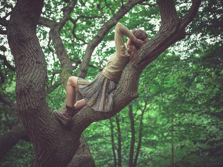 44084588-une-jeune-femme-est-couchée-sur-une-branche-d-un-arbre-dans-la-forêt.jpg