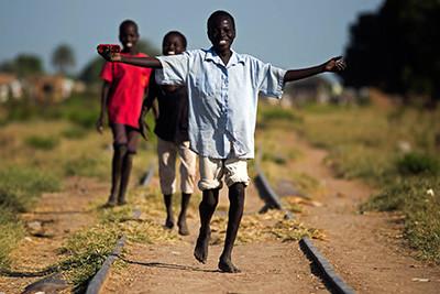 Un grup de nens camina per les vies del tren d'Aweil, al Sudan del Sud. Foto de l'Albert González Farran per al PNUD.