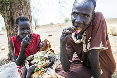 Dues dones i un nadó mengen fulles recollides dels arbres a Lankien, al Sudan del Sud. © Albert González Farran
