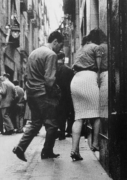 Una prostituta entra amb el seu client dins un edifici del barri del Raval.  ©Joan Colom