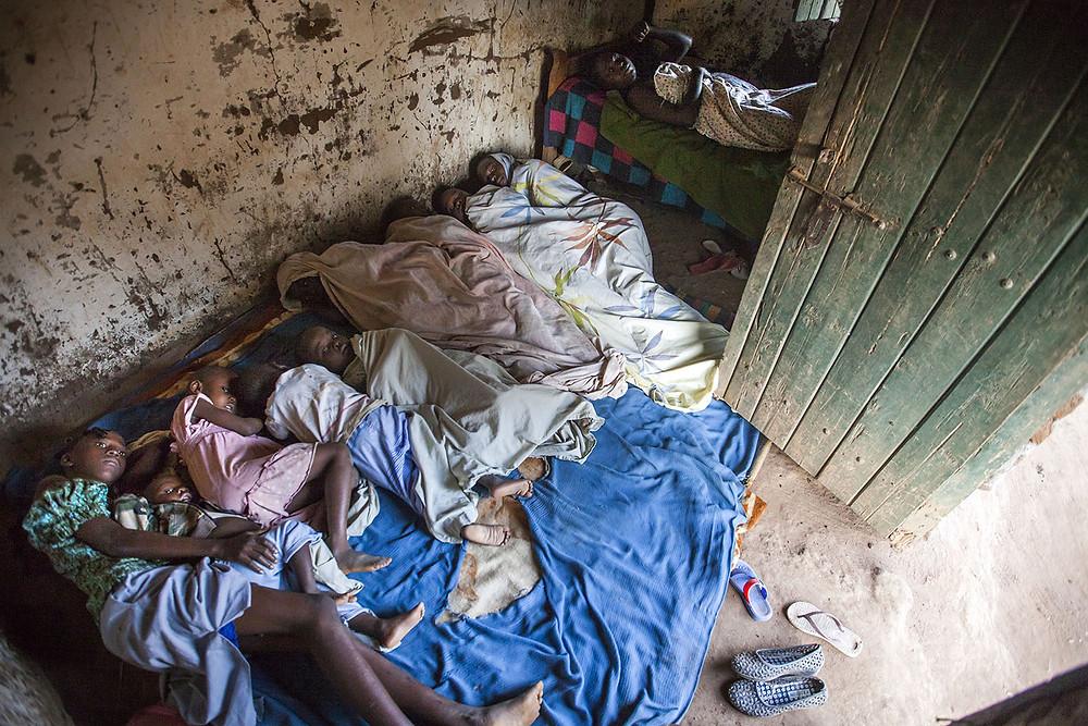 Nou nens i un adult dormen a l'habitació d'una casa de Yambio, Sudan del Sud, el gener de 2017. © Albert González Farran – UNICEF