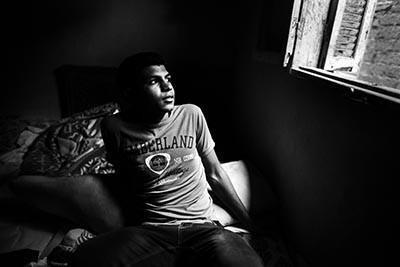 El Mahmud Abdul, de 17 anys, mira per la finestra de la seva habitació a Shobra Sandy (Egipte). © Albert González Farran / IOM