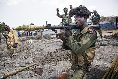 Un soldat sud-sudanès crida entusiasmat mentre carrega la seva arma a la trinxera dels afores de Lelo, al Sudan del Sud. Foto de l'Albert González Farran – AFP