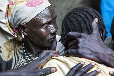 Nyakong Kiir abraça emocionada la seva jove Nyanom, greument malalta de malària a Padding, Sudan del Sud. Foto de l'Albert González Farran – AFP