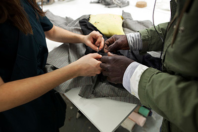 23 April 2015. Barcelona: 'Fodoy', from Gambia, attends practicals lessons of sewing by the owner (left) of a workshop in Barcelona, Spain. He has experience as a tailor back in his country and he wants to develop his skills. 'Fodoy' is a nickname for this migrant from Gambia, who arrived to Barcelona in 2007 without residence permit. He fled the country due to political prosecution and departed in a boat to Canary Islands. Then, the Spanish authorities reallocated him to Valencia and then to Barcelona. His asylum request has been blocked until 2017 due to having been condemned for drugs dealing. Until then, he is struggling to find accommodation and to have income to survive, although organizations such as CCAR assist him from time to time. Photo by Albert González Farran, CCAR
