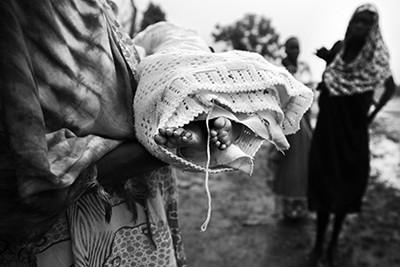 Una dona sosté el cos mort de la Nyanene, un nadó de cinc mesos que va morir de pneumònia en un atrotinat hospital de Maiwut, al Sudan del Sud. © Albert González Farran – CICR