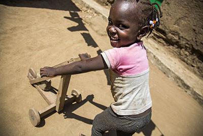 Una nena empeny un patí de fusta a casa seva a Juba, Sudan del Sud. Foto de l'Albert Gonzalez Farran / UNICEF