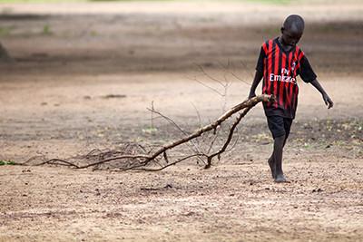 Un nen arrossega una branca cap a la cuina de l'escola de primària d'Aber (Sudan del Sud). Foto de l'Albert González Farran – WTI
