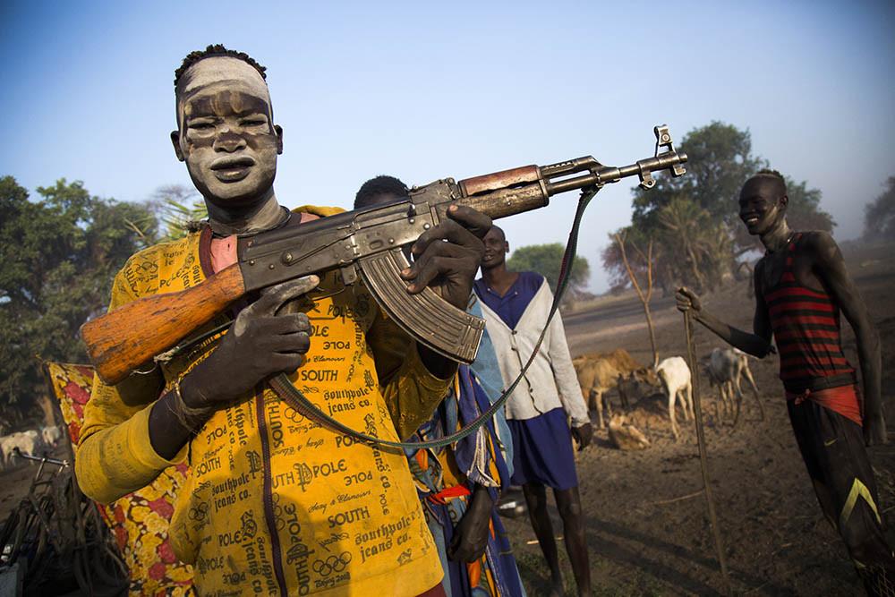 Un jove ramader sosté una metralladora al seu campament de Rumbek, al Sudan del Sud. © Albert González Farran.
