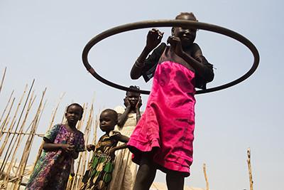 Una nena es tapa les orelles mentre una amiga juga amb el hula hoop al campament de desplaçats de Juba (Sudan del Sud). Foto de l'Albert González Farran