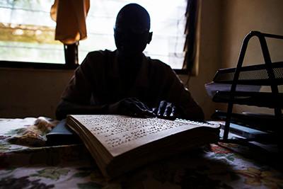 Levi Sunday, president de l'associació de cecs de Juba, Sudan del Sud, llegeix un llibre en Braille. Foto de l'Albert Gonzalez Farran, AFP