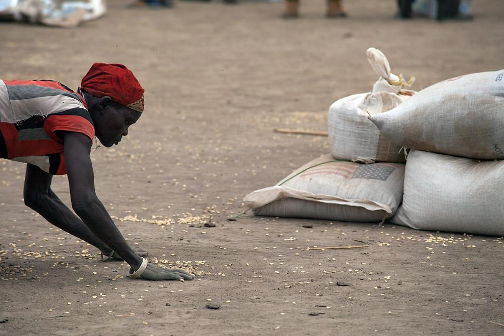 Una dona recull els grans que han caigut durant la distribució humanitària de cereals a Ganyiel, al Sudan del Sud. Foto de l'Albert González Farran – AFP.