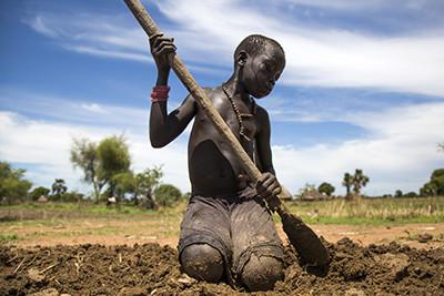 Nyibol Lual, una noia de 13 anys, ajuda la família a preparar la terra per cultivar-la a Panthau, al nord de Sudan del Sud. Foto de l'Albert González Farran – AFP