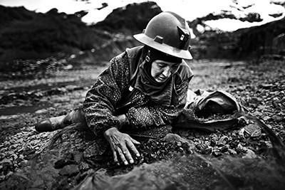 """Una """"Pallaquera"""" cerca or entre les pedres abocades fora d'una mina de La Rinconada, Ananea, Perú. Foto © Albert González Farran."""