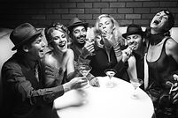 A group picture of friends talking and laughing with martinis and cigars.