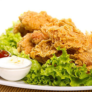 Image of fried chicken on a plate with sides of ranch and ketchup in small bowls.