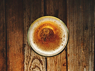 Vertical image of a pint of beer on top of a wooden bar.