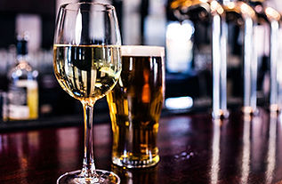 Image of a long stemmed glass of white wine and a pint of amber colored beer on a large wooden bar top.